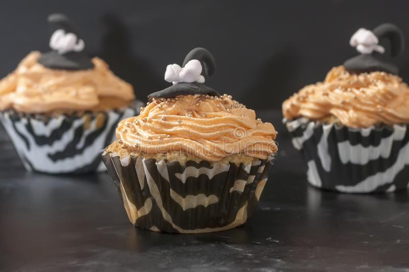 Happy Halloween orange and black decorated cupcake with a black witch hat and butter cream with beads. On a black background royalty free stock photography