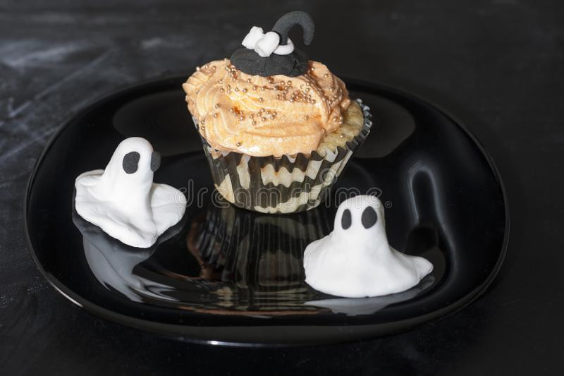 Happy Halloween with an orange and black decorated cupcake with a black witch hat and butter cream with beads. On a black haunted plate royalty free stock images