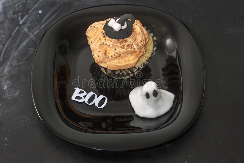 Happy Halloween orange and black decorated cupcake with a black witch hat and butter cream with beads on a black plate.  royalty free stock photo