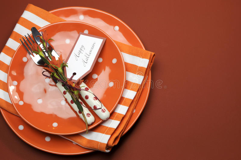 Happy Halloween orange polka dot and stripes dinner table setting, with copy space. Bright and modern Happy Halloween orange polka dot and stripes plates and stock images