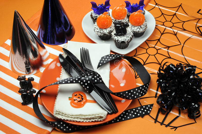Happy Halloween party table. With orange polka dot plates an chocolate cupcakes with black cat, pumpkin and bats decorations on orange background stock image