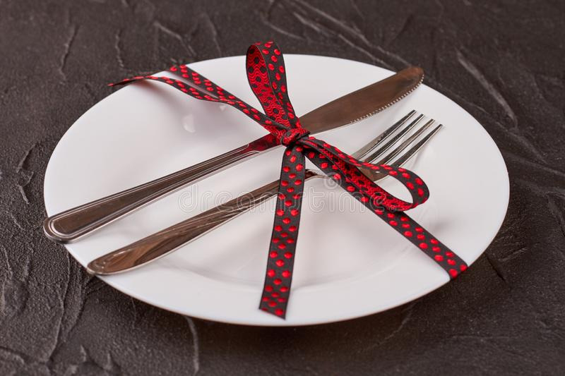 Happy Halloween party table setting. White plate, cutlery and black ribbon with red polka dots. Halloween holiday dish ware stock photo