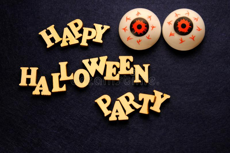 HAPPY HALLOWEEN PARTY and two balls of eye on a dark blue background. Words of wooden letters. Decoration for the holiday. HAPPY HALLOWEEN PARTY and two balls stock photo