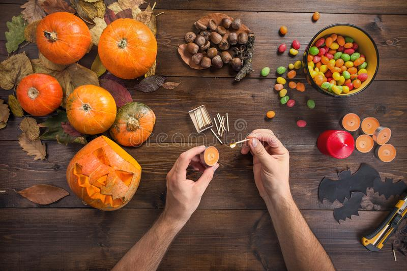 Happy Halloween! Preparations for the festival. Hands in the manufacturing process of a glowing lantern, igniting matches and candles. Top view from the first royalty free stock image
