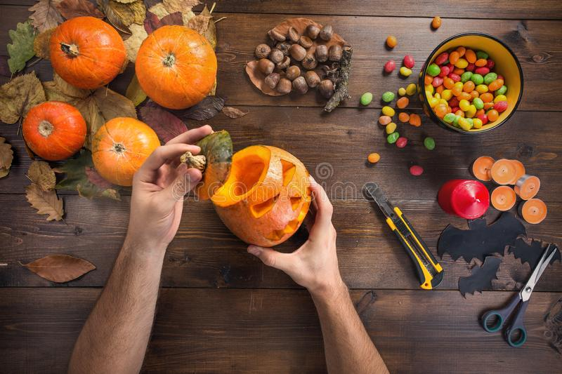 Happy Halloween! Preparing for the holiday. Hands in the process of making a glowing lantern, cutting a small orange pumpkin. Top view from the first person stock image
