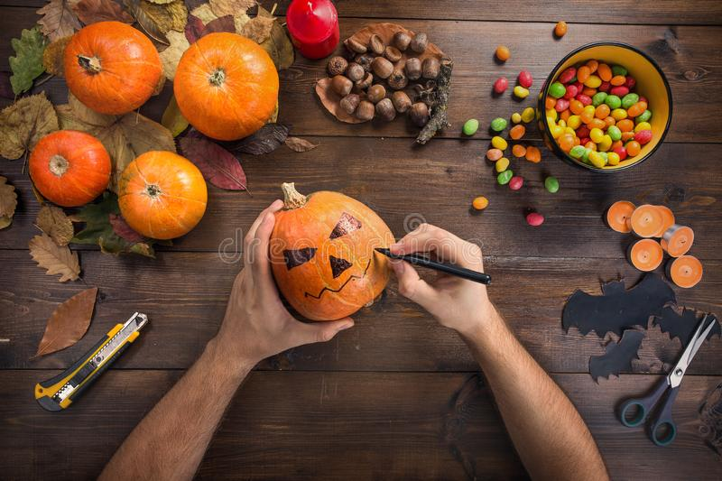 Happy Halloween! Preparing for the holiday. Hands in the process of making a glowing lantern, drawing on a pumpkin for cutting, next are the attributes of the stock photos