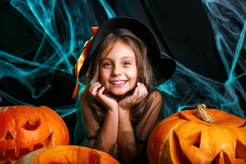 Happy halloween. Pretty little child girl in witch costume with carving pumpkin . Happy family preparing for Halloween. Happy halloween. Cute little child girl stock images