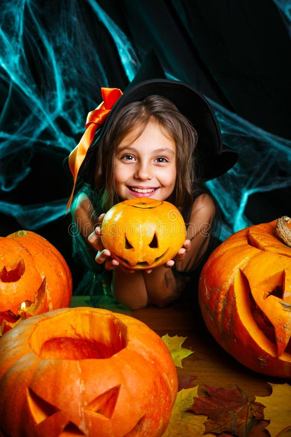 Happy halloween. Pretty little child girl in witch costume with carving pumpkin . Happy family preparing for Halloween. Happy halloween. Cute little child girl royalty free stock images