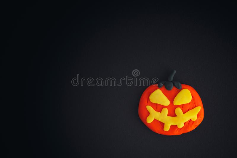 Happy Halloween. Halloween pumpkin on black background. Halloween pumpkin is made out of modeling clay royalty free stock photos