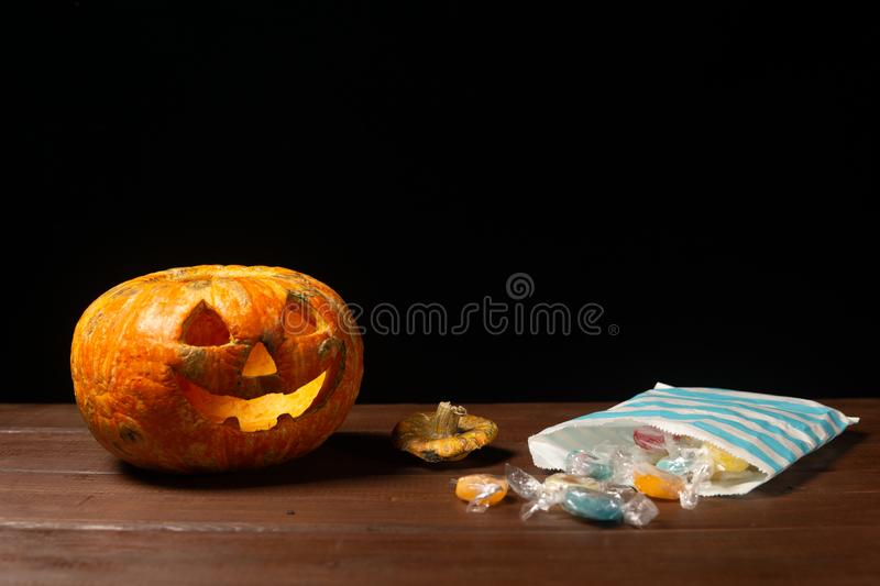 Happy Halloween pumpkin and candies. Trick or treat on a wooden table on a background of old wooden boards royalty free stock photos