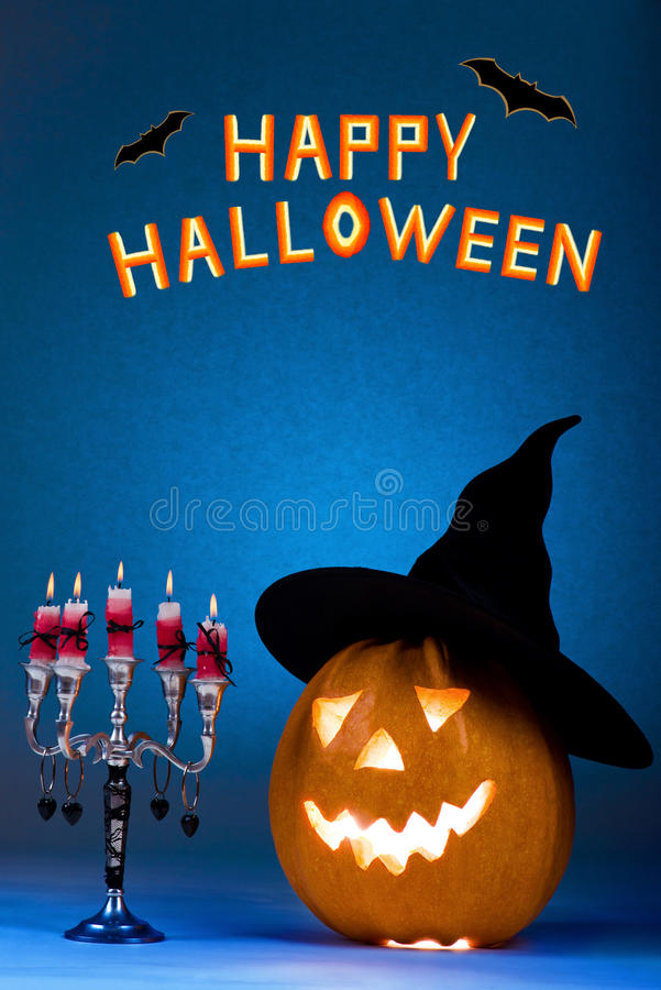 Happy Halloween pumpkin with a candlestick, funny face face on a blue background. royalty free stock photo