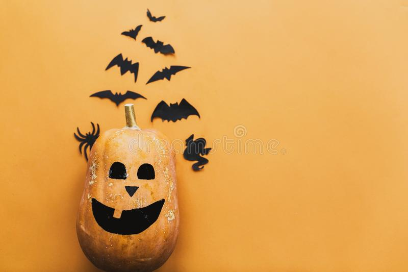 Happy Halloween. Pumpkin jack lantern and black bats, ghost, spider paper decorations on yellow background, copy space. Trick or. Treat concept. Halloween flat stock photos