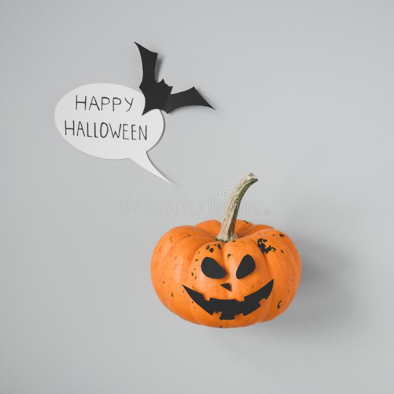 Happy halloween. Halloween pumpkin with speech bubble and bat on gray background.  royalty free stock photography