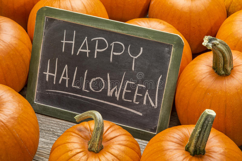 Happy Halloween with pumpkin. Happy Halloween - white chalk handwriting on a vintage slate blackboard surrounded by pumpkins stock photography