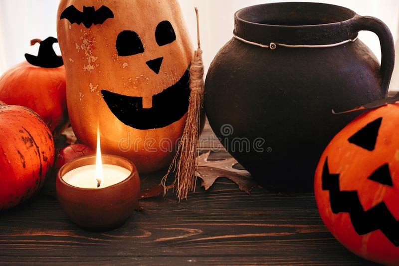 Happy Halloween. Pumpkins with scary faces with witch cauldron, bats, spider and burning candle  on dark wood. Jack o lantern royalty free stock images