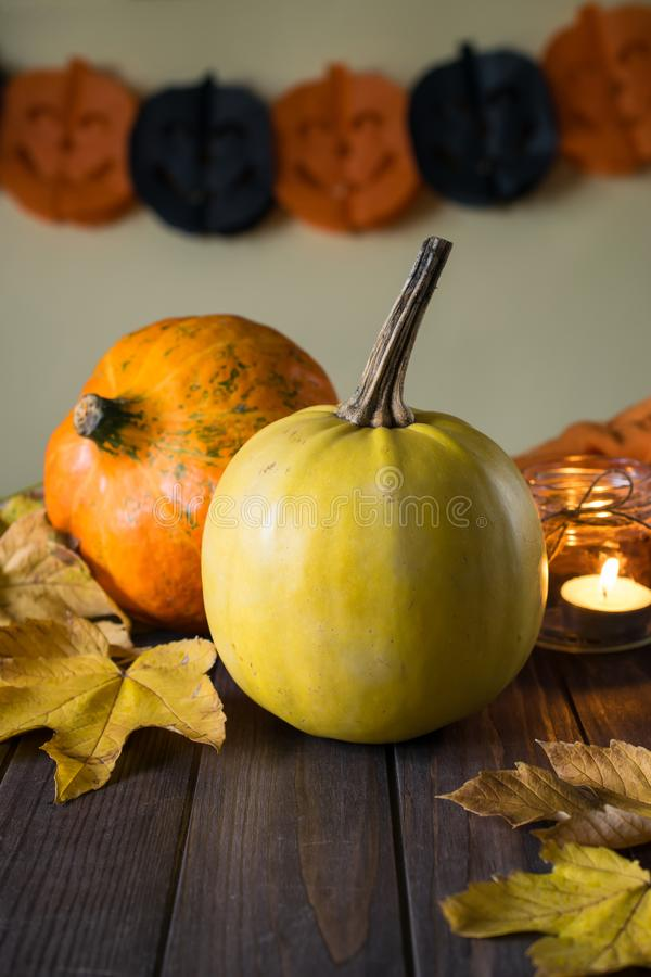 Happy Halloween pumpkins on wooden table with candle and autumn yellow leaves. Happy Halloween pumpkins on wooden table with candle and autumn leaves stock photos