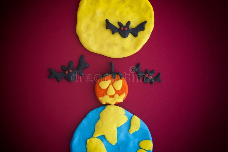 Happy Halloween Scene. Happy Halloween. The Moon, Earth, pumpkin and bats are made out of modeling clay royalty free stock image