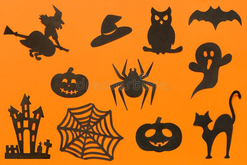 Happy Halloween Set silhouettes cut out of black paper on orange background. Happy Halloween Set cut out of black paper silhouettes pumpkin, witch, ghost, cat stock photo