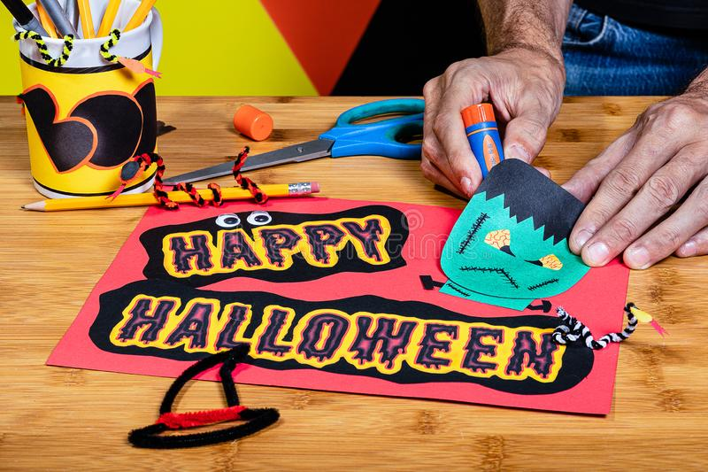 Happy Halloween Sign featuring Frankenstein, being made of construction paper by an adult. Surrounded by craft supplies and other. Halloween decorations royalty free stock images