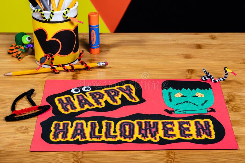 Happy Halloween Sign featuring Frankenstein, made of construction paper and surrounded by craft supplies and other halloween. Decorations.  The image has stock photos