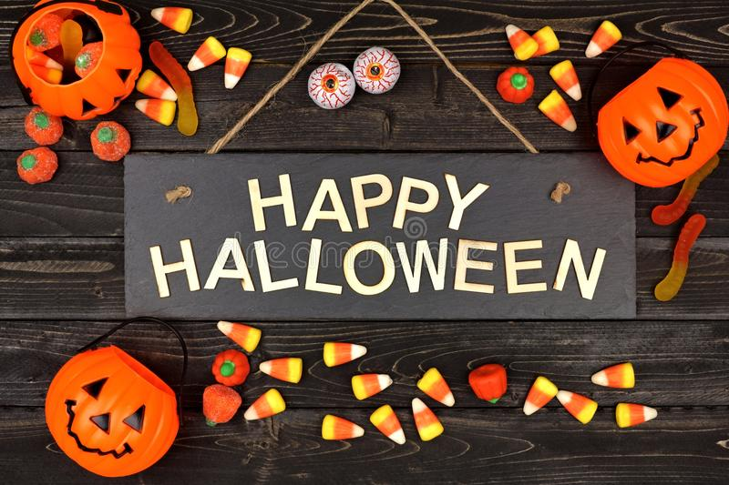 Happy Halloween sign and frame of candy on black wood stock photo