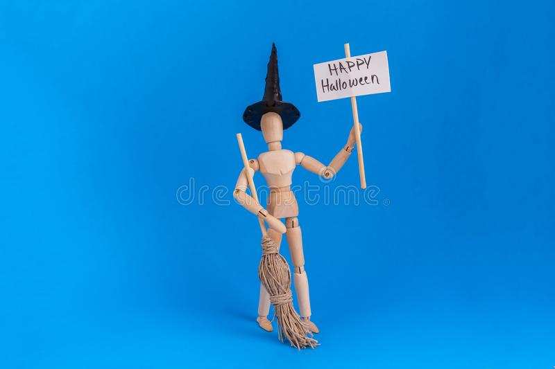 Happy Halloween sign held by jointed manikin dressed bin witches costume on blue background stock image