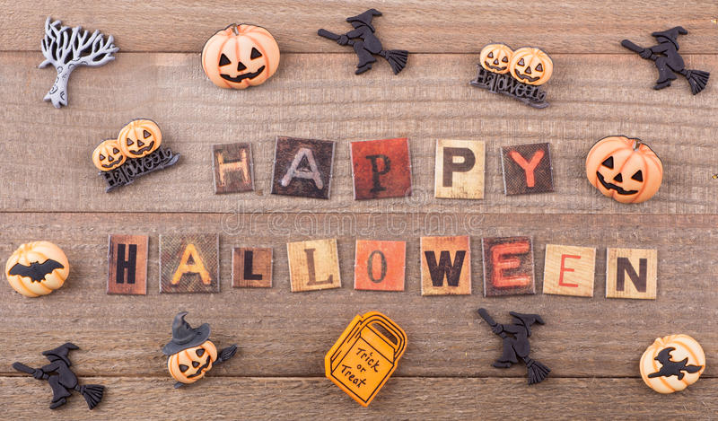 Happy Halloween Sign. Happy halloween text with halloween decorations on a wood background stock image