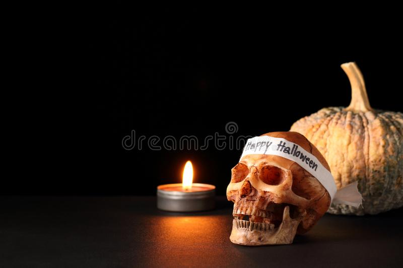 Happy Halloween. Smile skull with candle and pumpkin on black table in black background / skull wearing headband with text ` Happy Halloween stock photography