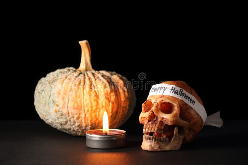 Happy Halloween. Smile skull with candle and pumpkin on black table in black background / skull wearing headband with text ` Happy Halloween royalty free stock photography