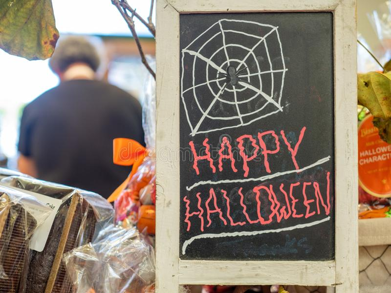 Happy Halloween spider web sign written in chalk on board at store with cashier in background stock image