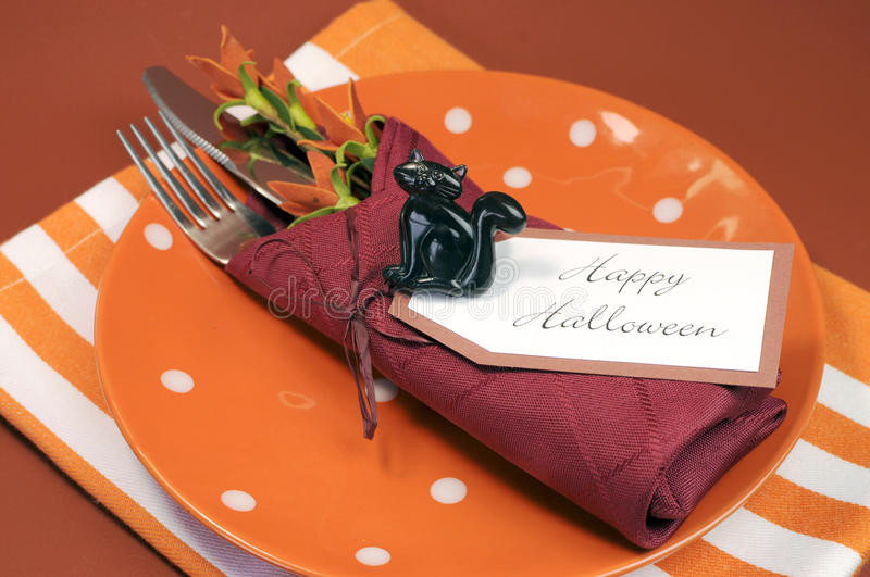 Happy Halloween table place setting with orange polka dot and stripe plate and napkin. And black cat decoration against autumn fall colors background stock photo