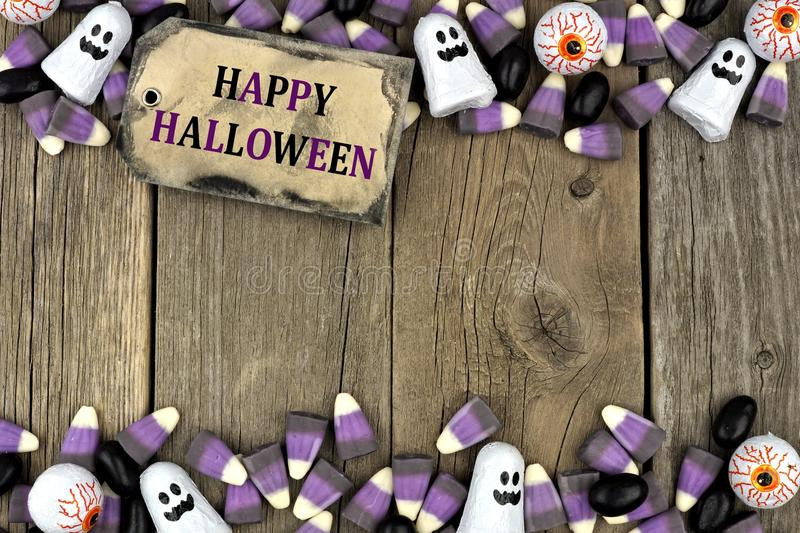 Happy Halloween tag with candy double border over aged wood. Happy Halloween tag with candy double border against an aged wood background royalty free stock photography