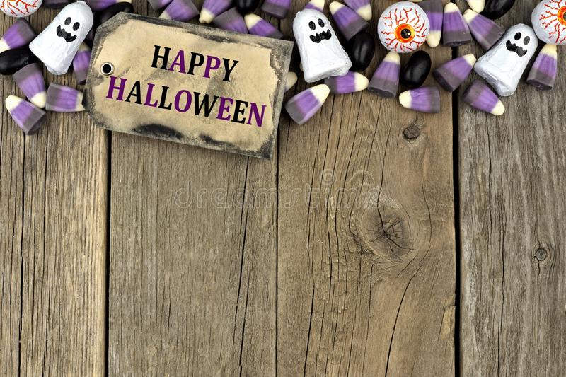 Happy Halloween tag with candy top border over aged wood. Happy Halloween tag with candy top border against an aged wood background royalty free stock image