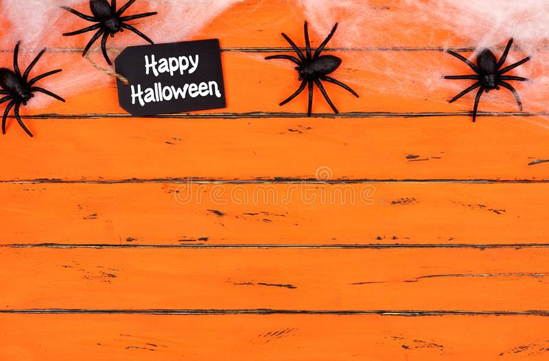 Happy Halloween tag with spider web top border on orange wood stock images