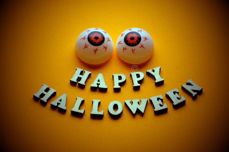 HAPPY HALLOWEEN. A cheerful face with emotion from wooden letters and two balls of eye on a bright orange background. Template for. HAPPY HALLOWEEN. Template for stock photography