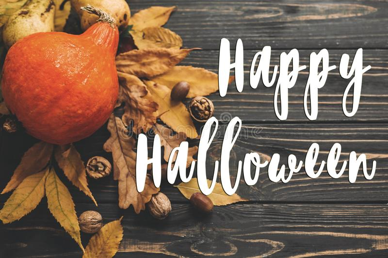 Happy Halloween Text on Beautiful Pumpkin with bright autumn lea. Ves, acorns, nuts on wooden rustic table, flat lay. Atmospheric image. Seasons greeting card stock image