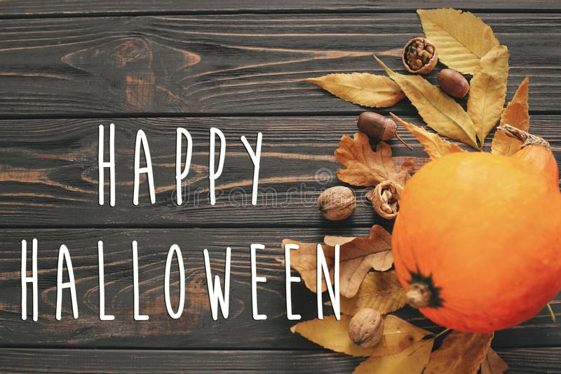 Happy Halloween Text on Beautiful Pumpkin with bright autumn lea. Ves, acorns, nuts on wooden rustic table, flat lay. Atmospheric image. Seasons greeting card stock images