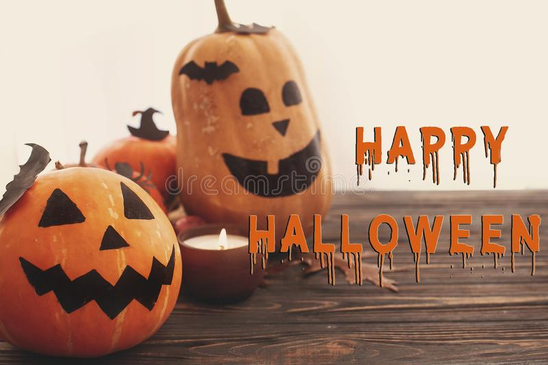 Happy Halloween text, bloody sign on pumpkins, jack-o-lantern,. Witch cauldron, bats, spider, candle, autumn leaves on black wood in light. Halloween decoration stock photo