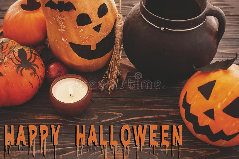 Happy Halloween text, bloody sign on pumpkins, jack-o-lantern, w. Itch cauldron,bats, spider, candle,ghost, autumn leaves on dark background. Space for text royalty free stock photography