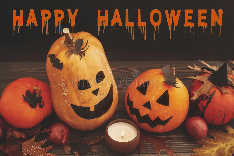 Happy Halloween text, bloody sign on pumpkins, jack-o-lantern, w. Itch cauldron,bats, spider, candle,ghost, autumn leaves on dark background. Space for text stock images