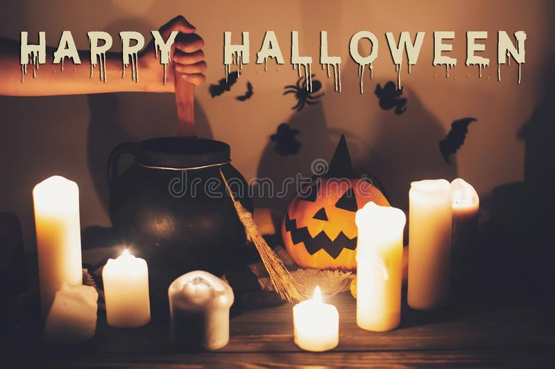 Happy Halloween text concept. Spooky Halloween sign. Witch hand. Boiling potion spell in cauldron, Jack o lantern, pumpkin,candles, broom and bats, ghosts in royalty free stock images