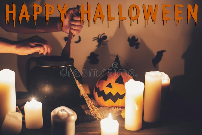 Happy Halloween text concept. Spooky Halloween sign. Witch hand. Boiling potion spell in cauldron, Jack o lantern, pumpkin,candles, broom and bats, ghosts in royalty free stock photo