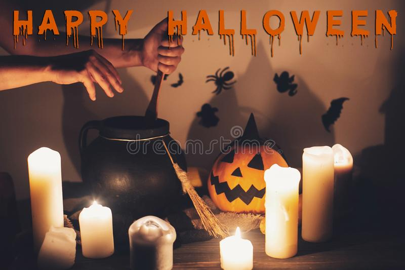 Happy Halloween text concept. Spooky Halloween sign. Witch hand. Boiling potion spell in cauldron, Jack o lantern, pumpkin,candles, broom and bats, ghosts in stock photography