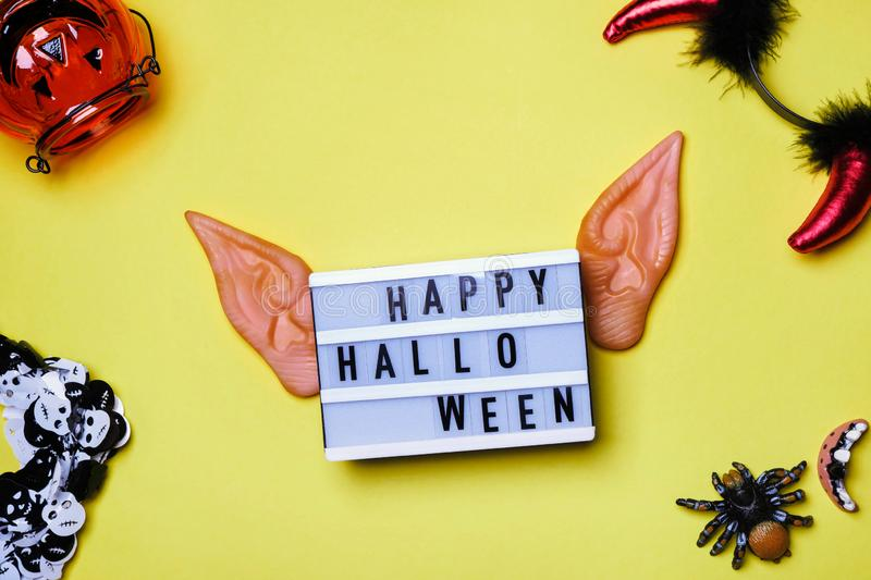 Happy Halloween text and elven ears, party inventory. Halloween words on white board, devil horns, spider, pumpkin royalty free stock image