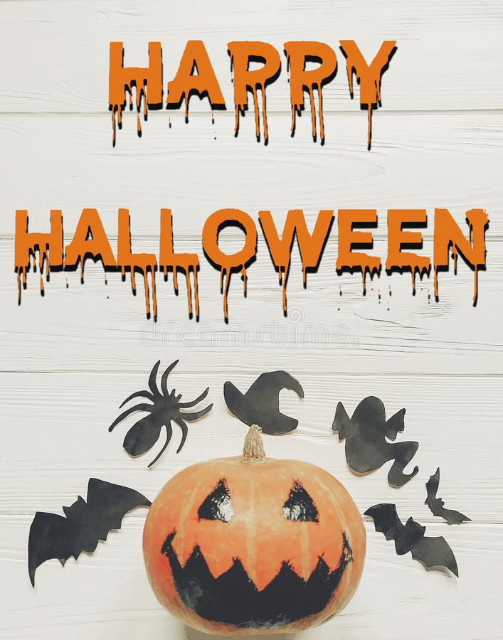 Happy halloween text flat lay. jack lantern pumpkin with witch g. Host bats and spider black decorations on white wooden background top view, space for text stock photography