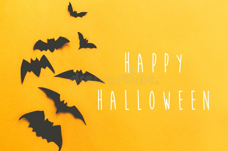 Happy Halloween text, greeting card. Black bats flying on bright yellow paper background. Flat lay. Modern spooky minimal royalty free stock image