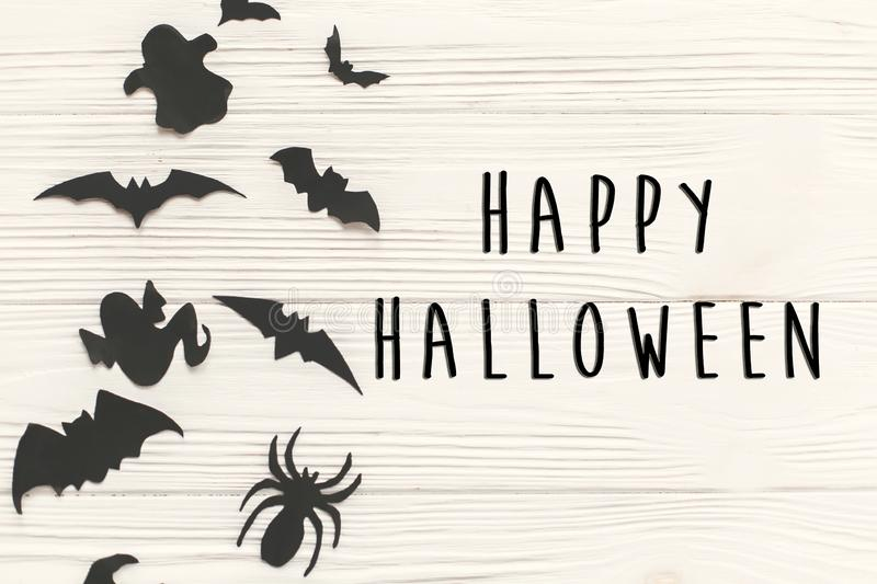 Happy Halloween text sign, flat lay. Black paper bats, spiders,. Ghosts top view on white rustic wooden background. Space for text. Season`s greeting card royalty free stock image