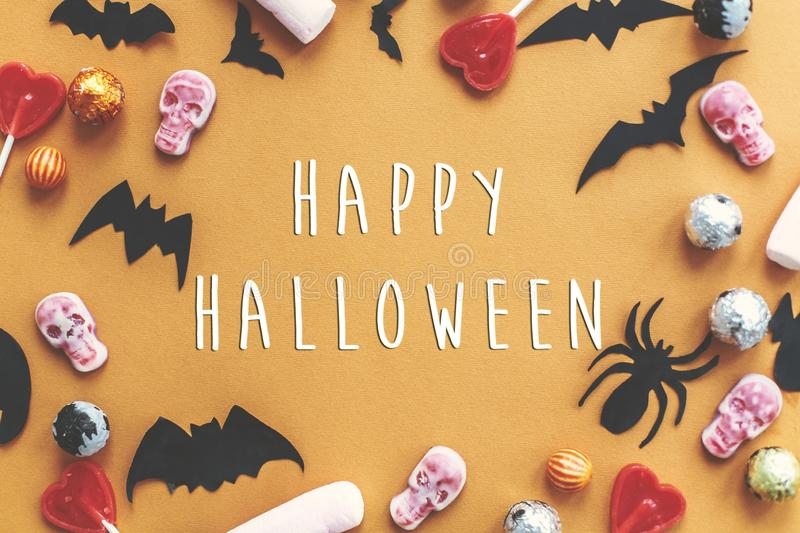 Happy Halloween text sign, flat lay. Holiday candy border with b. Ats, spiders, skulls top view. Trick or treat. Season`s greeting card stock photos
