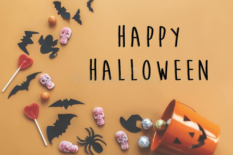 Happy Halloween text sign, flat lay. Jack o Lantern bucket with. Holiday spilling candy, bats,spiders, skulls on orange paper. Space for text. Season`s greeting stock image