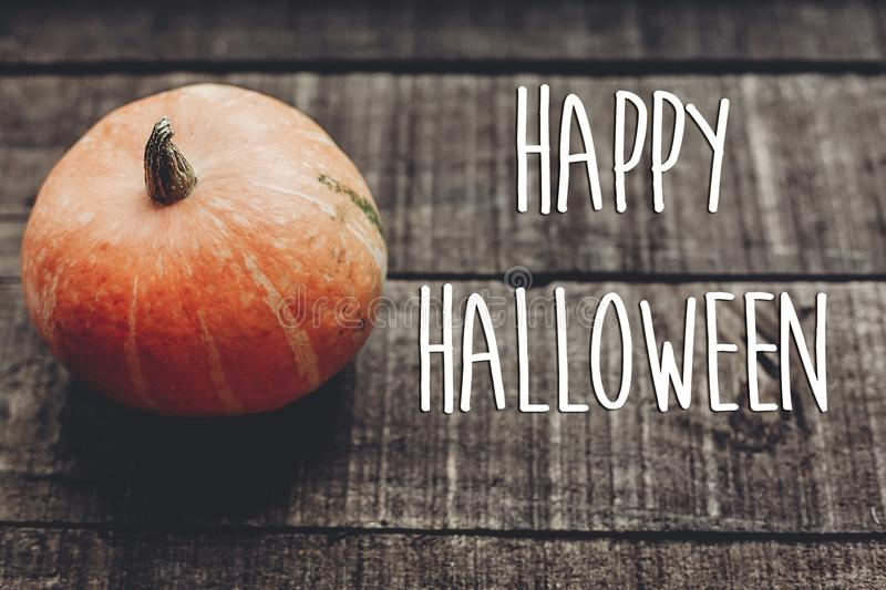 Happy halloween text sign, greeting card. simple fall image flat. Lay. beautiful pumpkin on rustic wooden background, top view. cozy autumn mood. fall holiday royalty free stock image